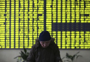 A stock investor pauses near a display board showing stock prices in green to symbolize a fall in price at a brokerage house in Jiujiang in central China's Jiangxi province Monday Jan. 4, 2016. (Chinatopix Via AP) CHINA OUT