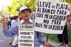 "Argentines protest against the Supreme Court and it's backing of the banking curbs imposed to halt a run on the banks, in front of the court building, January 10, 2002. Analysts said that freezing Argentine's savings may save the creaking banking system from collapse but public confidence is dead, putting the banks themselves at risk. The larger sign says, ""I took my money to the bank so they would take care of it, not so they would steal it."" REUTERS/Rickey Rogers"