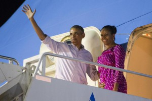 President Barack Obama, left, and first lady Michelle Obama wave as they board Air Force One to depart from Joint Base Pearl Harbor-Hickam at the end of their family vacation, on Saturday, Jan. 2, 2016, in Honolulu, Hawaii. (ANSA/AP Photo/Evan Vucci)