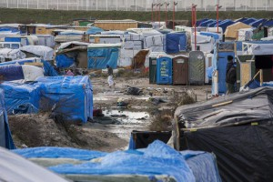 A migrant walks among the tents and huts of the makeshift camp called 'The Jungle' next to the fenced area made of containers used as housing in Calais, France, 15 February 2016. EPA/JULIEN WARNAND