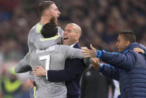 Real Madrid's Cristiano Ronaldo (C) celebrates with his teammate Sergio Ramos (L) and his head coach Zinedine Zidane (R) after scoring the 0-1 goal during the UEFA Champions League Round of 16 first leg soccer match between AS Roma and Real Madrid CF at the Olimpico stadium in Rome, Italy, 17 February 2016.. ANSA/CLAUDIO PERI