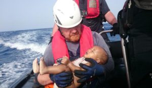 In this Friday, May 27, 2016 photo, a Sea-Watch humanitarian organization crew member holds a drowned migrant baby, during a rescue operation off the coasts of Libya. Survivor accounts have pushed to more than 700 the number of migrants feared dead in Mediterranean Sea shipwrecks over three days in the past week, even as rescue ships saved thousands of others in daring operations. (Christian Büttner/EIKON NORD GMBH GERMANY via AP)