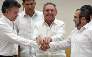 TOPSHOTS Colombian President Juan Manuel Santos (L) and the head of the FARC guerrilla Timoleon Jimenez, aka Timochenko (R), shake hands as Cuban President Raul Castro (C) holds their hands during a meeting in Havana on September 23, 2015.  AFP PHOTO / Luis Acosta