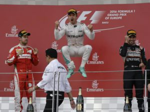 Mercedes driver Nico Rosberg of Germany, center, winner of the race, jumps in celebration on the podium, flanked by second place Ferrari driver Sebastian Vettel of Germany, left, and third place Force India driver Sergio Perez of Mexico, during the Formula One Grand Prix of Europe at the Baku circuit, in Baku, Azerbaijan, Sunday, June 19, 2016.  (ANSA/AP Photo/Luca Bruno)