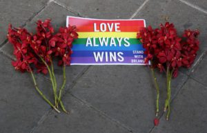 A sign and flowers lie on the ground outside the US Embassy during a vigil for those killed and wounded in the Sunday June 12, 2016 mass shooting at a gay nightclub in Orlando, Florida, in Bangkok, Thailand, Monday, June 13, 2016.