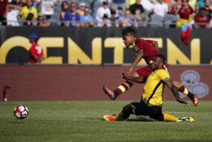 Venezuela's Josef Martinez , top,  takes a shot on goal under pressure from Jamaica's Wes Morgan during a Copa America Centenario Group C soccer match at Soldier Field in Chicago, Sunday, June 5, 2016. (ANSA/AP Photo/Charles Rex Arbogast)