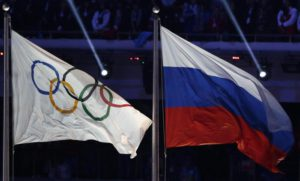 FILE- In this Feb. 23, 2014, file photo, the Russian national flag, right, flies after next to the Olympic flag during the closing ceremony of the 2014 Winter Olympics in Sochi, Russia.  (ANSA/AP Photo/Matthias Schrader, File)