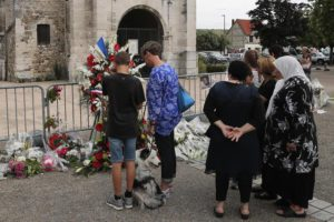 Residents pay tribute at a makeshift memorial in front of the Saint Etienne church where Priest Jacques Hamel was killed on 26 July in a hostage taking in Saint-Etienne-du-Rouvray, Normandy, France, Thursday, July 28, 2016. The second man who attacked a Normandy church during a morning Mass this week, slitting the throat of the elderly priest, is a 19-year-old Frenchman from eastern France, the prosecutor's office said Thursday. (ANSA/AP Photo/Francois Mori)