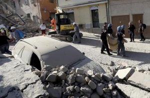 A body is carried away as a car is covered in rubble after an earthquake, in Amatrice, central Italy, Wednesday, Aug. 24, 2016. (ANSA/AP Photo/Alessandra Tarantino)