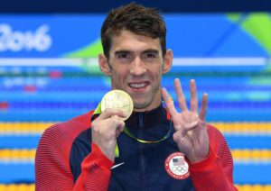 Michael Phelps of USA celebrates his fourth Rio 2016 gold medal during the medal ceremony for the men's 200m Individual Medley Final race of the Rio 2016 Olympic Games Swimming events at Olympic Aquatics Stadium at the Olympic Park in Rio de Janeiro, Brazil, 11 August 2016.  EPA/DEAN LEWIS