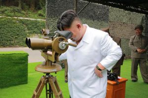 This undated photo distributed on Tuesday, Sept. 6, 2016, by the North Korean government shows North Korean leader Kim Jong Un looking though binoculars at the site of a ballistic missile launching at an undisclosed location in North Korea.  (Korean Central News Agency/Korea News Service via AP)