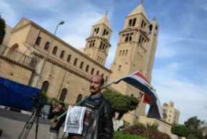 An Egyptian man holds a poster for Boutros Boutros-Ghali the former Secretary-General of the United Nations outside the Saints Peter and Paul Coptic Orthodox church in Abassya district, in Cairo, Egypt, 18 February 2016. EPA/MOHAMED HOSSAM
