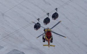 An EC-135 helicopter operated by the French Societe' Civile hovers, Friday, Sept. 9, 2016, near three cars of the Panoramic Mont Blanc cable car that stalled around 4 p.m. (1400 GMT) on Thursday, after its cables reportedly tangled.  (ANSA/AP Photo/Luca Bruno)