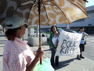 Polly Usher is provided with the latest police killing story as protestors holds a  sign that reads 'Stop Police Killings' during a demonstration in Los Angeles, California, USA, 07 July 2016. EPA/MIKE NELSON