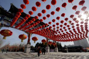People walk past an entrance gate of Ditan Park decorated with red lanterns ahead of the Chinese Lunar New Year in Beijing, Tuesday, Feb. 2, 2016. Chinese will celebrate the Lunar New Year on Feb. 8 this year which marks the Year of Monkey on the Chinese zodiac. (ANSA/AP Photo/Andy Wong)