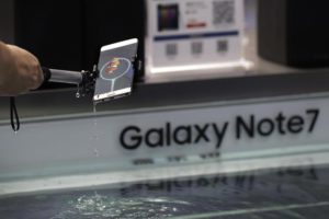 FILE - In this Thursday, Sept. 1, 2016 file photo, a man holds a Samsung's latest Galaxy Note 7 smartphone after dipping it in water to test its waterproofing features at a roadshow booth outside a shopping mall in Beijing. (ANSA/AP Photo/Andy Wong, File)
