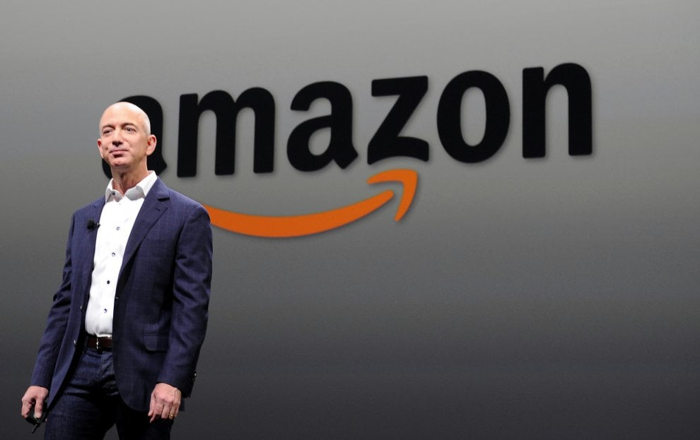 Jeff Bezos in primo piano, dietro il simbolo di Amazon
