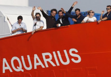 Migranti salutano dal bordo dell'Aquarius.