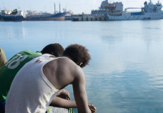 Due migranti seduti sul bordo di una banchina di un porto. Amnesty