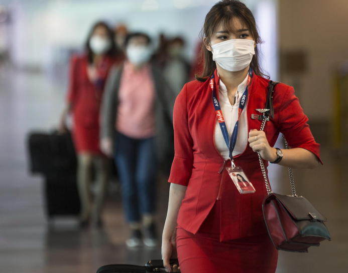Hostess di AirAsia in transito all'aeroporto con la mascherina sul viso.